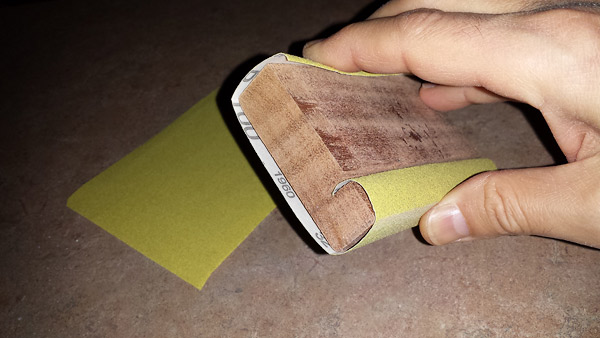 A piece of sanding paper wrapped around the sanding block