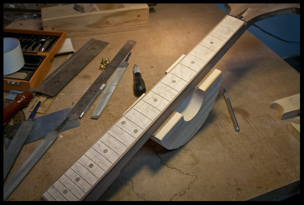 Maple fretboard with walnut fret markers and binding