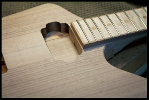 The neck heel in the neck pocket with humbucker cavity