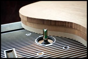 Routing the guitar shape with a flush trim router bit
