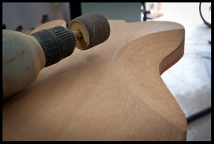 Rough carving the belly contour on the Telecaster with a sanding disk on the drill