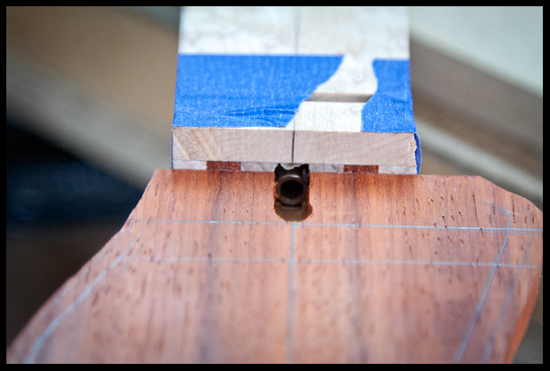 The headstock veneer is glued on and a opening is made for access to the truss rod