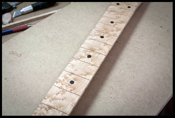After sanding the ebony dots inlays flush with the fretboard