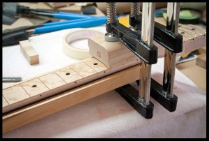 Hammering in the frets and then clamping them