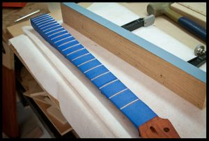 Taping the fretboard before leveling the frets