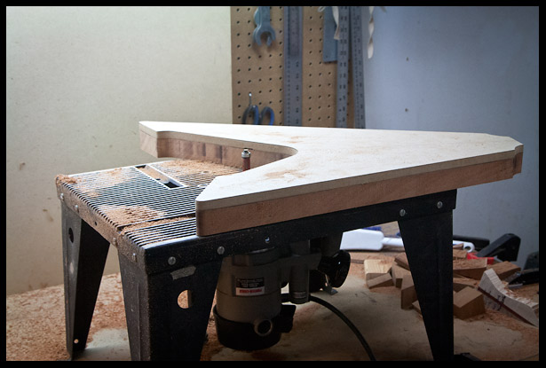 Routing the body shape on the router table with the MDF template as a guide
