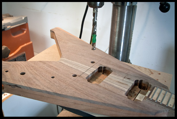 Once the neck is glued in, I calculate and drill the holes for bridge posts