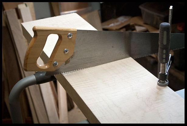 Hand sawing a piece of flamed maple